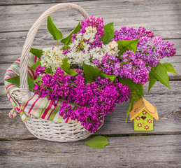 White basket with a branch of lilac