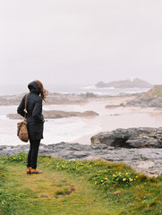 A woman lookng over the rocks and the shoreline on a windy day by the sea.