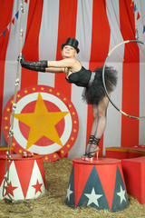 Actress in black tutu and top hat stands on pedestal