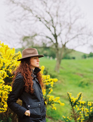 A woman with long curly hair wearing a hat, by a flowering gorse bush.