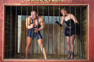 Strong man and beautiful woman in cage for animals