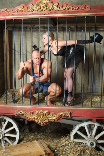 Poster Beautiful girl calms furious athlete in cage for animals