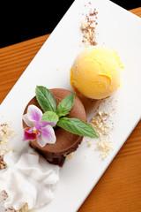 Chocolate souffle with mango ice cream and coconut foam
