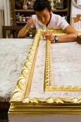 Female artisan working on an elegant wood frame