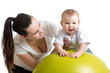 mother with baby having fun with  gymnastic ball