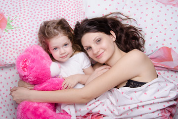 Mom and daughter lying in bed