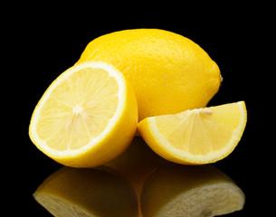Studio shot sliced three lemons isolated on black