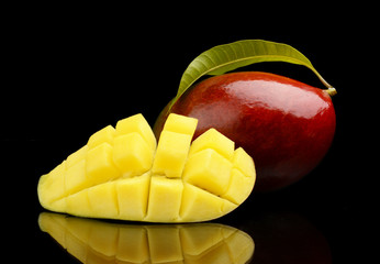 Ripe mango with slice and leaf isolated black background