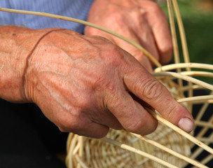 skilled craftsman who works the cane to create a wicker basket