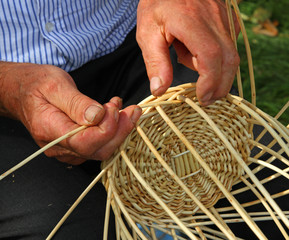 Elder's hands working the cane to create a wicker basket