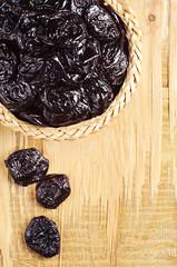 Prunes in wicker bowl closeup