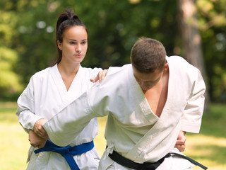Young woman and man practicing karate outdoors