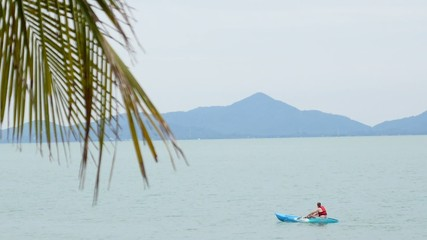 Man in Kayak in the Sea against Island Silhouette.
