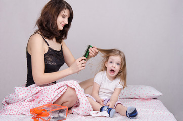 Mom combing hair-year old daughter