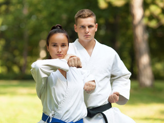 Two people practicing karate outdoors