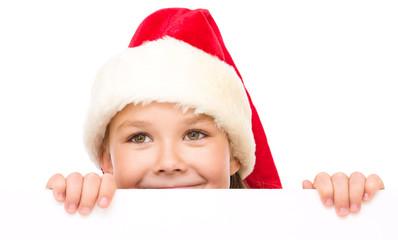 Little girl in santa hat is holding blank board