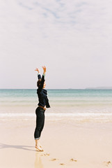 A woman standing barefoot on the sand raising her arms above her head, in a gesture.
