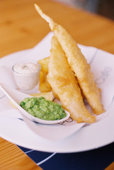 Traditional food, fried battered fish and chips, with mushy peas and tartare sauce on a plate.