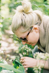 A woman leaning down to examine a flowerhead.