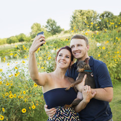 A couple playing with their small dog in the park, taking a selfy.