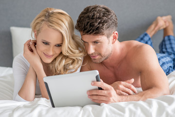 Sweet Couple on Bed Watching Something in Tablet