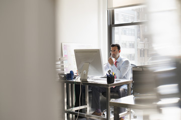 A man seated at a desk in an office, using a computer.