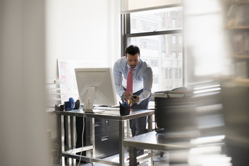 A man standing at his desk using his phone, dialling or texting.