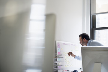 A man using a pen to mark a wall chart or project plan on an office wall.