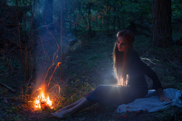 beautiful witch looking at the fire in the forest
