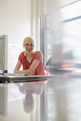 Office life. A young woman sitting at an office desk smiling.
