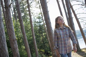 A girl walking in woodland beside a lake in summer.