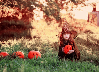 little girl in halloween costume with jack pumpkin