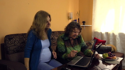Young pregnant woman teach her grandmother computer skills