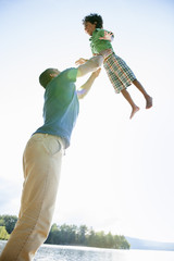 A man lifting a small boy up above his head in play.