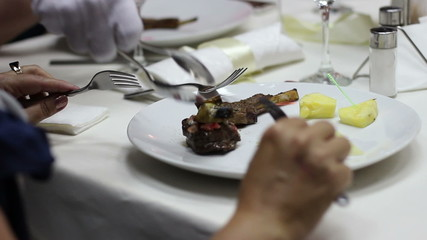 waiter puts the meat to plate visitor