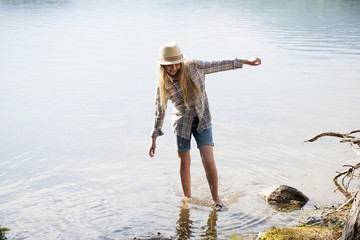 A girl in a straw hat paddling in the shallow waters of a mountain lake.