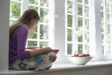 Girl sitting by a window, reading a book.