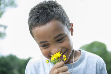 Boy smiling and holding flower.