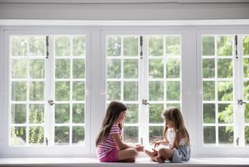Two girls sitting indoors cross legged.