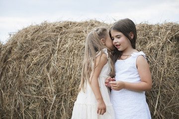 Two girls whispering playing outdoors