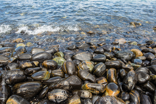 Leinwanddruck Bild The black stone in the beach of southern Thailand
