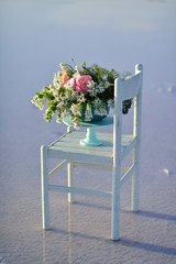 on the shore of the salt sea is a wooden chair with a vase of fl