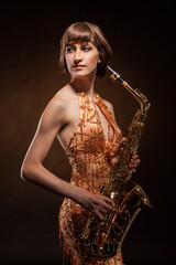 Sexual young woman posing with saxophone at studio