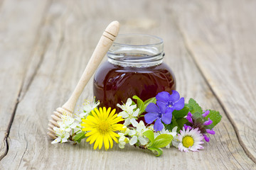 Honey in a jar and flowers on wooden background