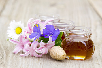 Honey in jars, flowers and honey dipper on wooden background