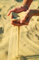 sand pours out of the female hands
