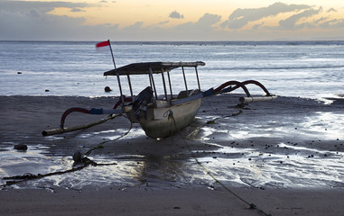 Empty Indonesian fishing boat at the shore, low-tide, sunrise