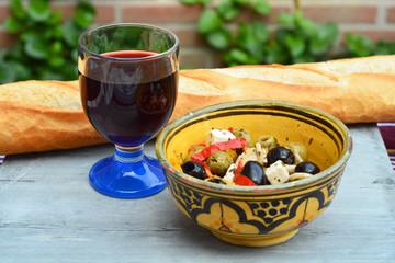 Een schaaltje olijven met stokbrood en rode wijn.