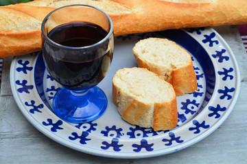 stokbrood en rode wijn op een blauw bord