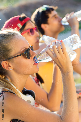canvas print picture Group of friends drinking water in the park.